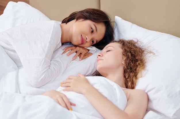 Szczęśliwa młoda ładna wietnamska kobieta zakochana, patrząc na swoją śpiącą dziewczynę