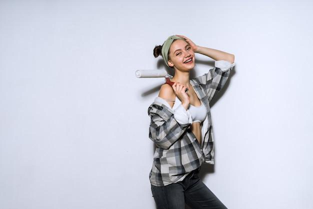 Szczęśliwa młoda malarka trzymająca poduszkę do malowania ścian, śmiejąca się, robiąca naprawy w swoim nowym mieszkaniu