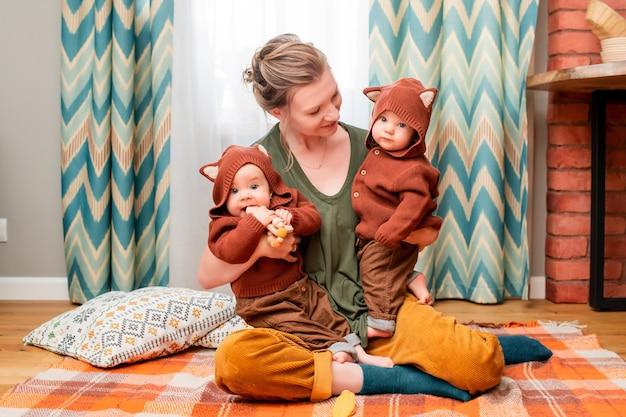 Szczęśliwa młoda mama bawi się z dziećmi bliźniakami siedzi na kocu w domu