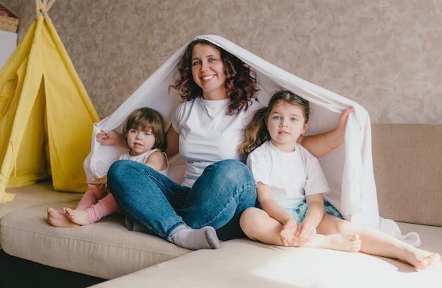 Szczęśliwa młoda mama i dwie małe córeczki bawią się razem na sofie przykrytej prześcieradłem. szczęśliwe relacje rodzinne.