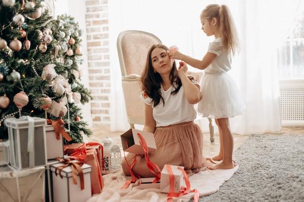 Szczęśliwa młoda mama i jej córeczka w ładnej sukience siedzą przy drzewie noworocznym i otwierają noworoczne prezenty w jasnym, przytulnym pokoju.