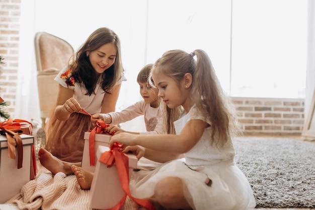 Szczęśliwa młoda mama i jej dwie urocze córki w ładnych sukienkach siedzą na dywanie i otwierają noworoczne prezenty w jasnym, przytulnym pokoju.