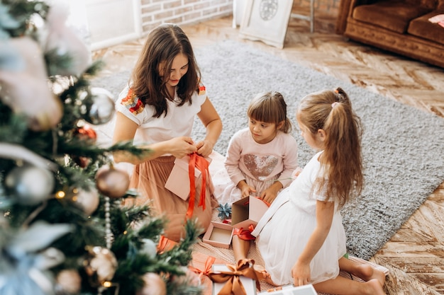 Szczęśliwa młoda mama i jej dwie urocze córki w ładnych sukienkach siedzą przy drzewie noworocznym i otwierają noworoczne prezenty w jasnym, przytulnym pokoju.