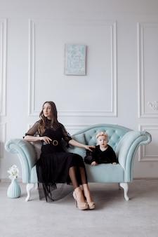 Szczęśliwa młoda mama na stylowej kanapie odpoczywa z małą córeczką w czarnych sukienkach i pozie, uśmiechnięta matka i dziewczynka bawią się w studio. wygląd rodziny