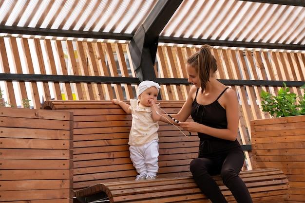 Szczęśliwa młoda mama z małą córką bawiącą się na ławce w parku