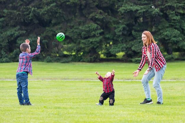 Szczęśliwa młoda matka bawi się piłką z dzieckiem w parku na zielonym trawniku
