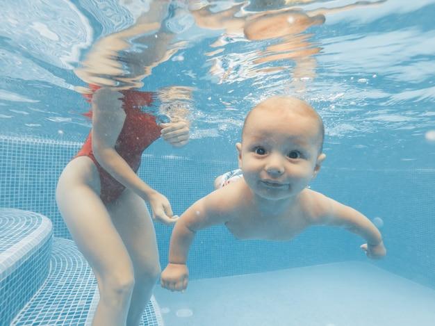 Szczęśliwa młoda matka bawi się z dzieckiem w odkrytym basenie w gorący letni dzień. strzelanie pod wodą