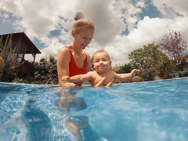 Szczęśliwa młoda matka bawi się z dzieckiem w odkrytym basenie w gorący letni dzień