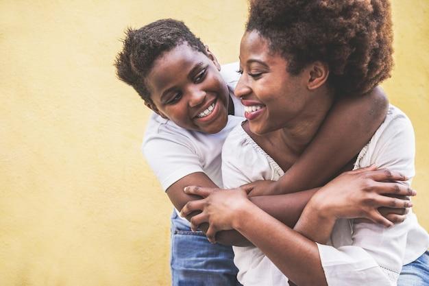 Szczęśliwa młoda matka bawi się ze swoim dzieckiem - syn tuli matkę na zewnątrz - pojęcie rodzinnego stylu życia, macierzyństwa, miłości i delikatnych chwil - skup się na twarzy dziecka