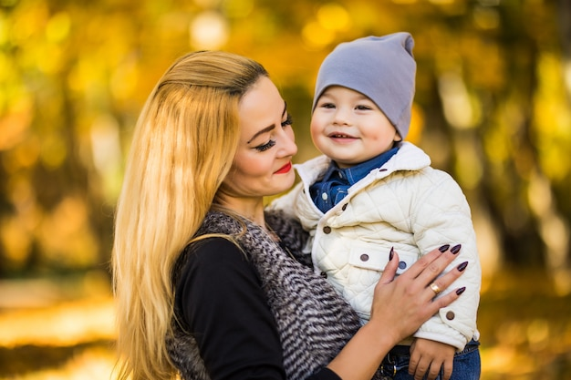 Szczęśliwa młoda matka bawi się ze swoim małym synkiem na słońce ciepły jesienny lub letni dzień. piękne światło słońca w ogrodzie jabłkowym lub w parku. szczęśliwa rodzina koncepcja