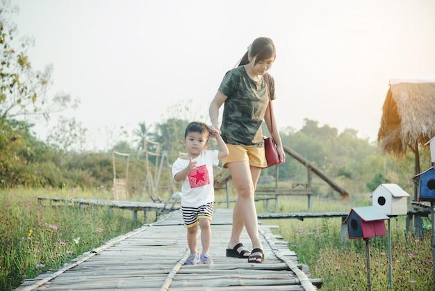 Szczęśliwa młoda matka gra i zabawy z jej mały synka w parku w słoneczny letni dzień