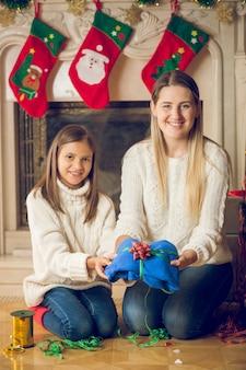 Szczęśliwa młoda matka i córka siedzą na podłodze przy kominku i pakują sweter na boże narodzenie