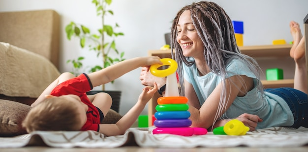 Szczęśliwa młoda matka i jej dziecko razem zbierają kolorową piramidę