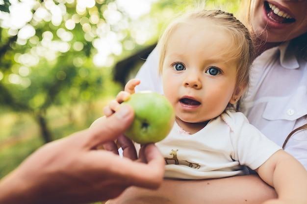 Szczęśliwa młoda matka i urocza córka trzyma jabłko