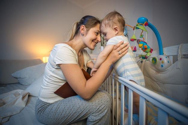 Szczęśliwa młoda matka patrząca na swoje dziecko w łóżeczku przed pójściem spać