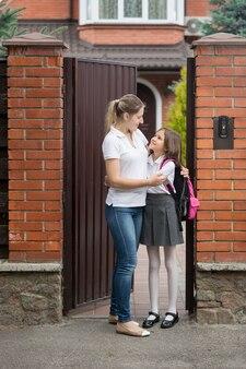 Szczęśliwa młoda matka przytulająca się z córką przed pójściem do szkoły