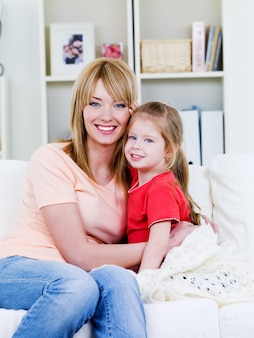 Szczęśliwa młoda matka siedzi na kanapie i obejmuje swoją kochającą córeczkę - w pomieszczeniu