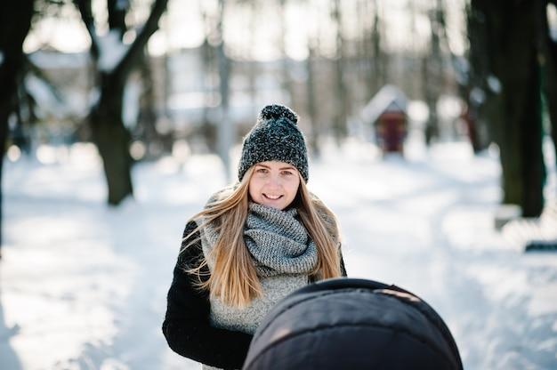 Szczęśliwa młoda matka spaceruje z wózkiem i dzieckiem w zimowym parku