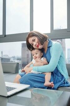Szczęśliwa młoda matka spędza czas z małą córką podczas oglądania prezentacji produktu na ekranie laptopa