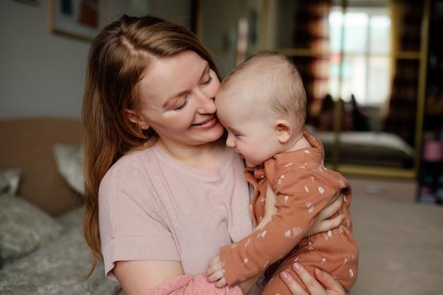 Szczęśliwa młoda matka z dzieckiem w ramionach koncepcja szczęśliwego macierzyństwa rodzinnego