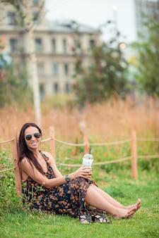 Szczęśliwa młoda miastowa kobieta pije kawę outdoors