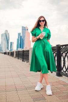 Szczęśliwa młoda miastowa kobieta pije kawę w europejskim mieście