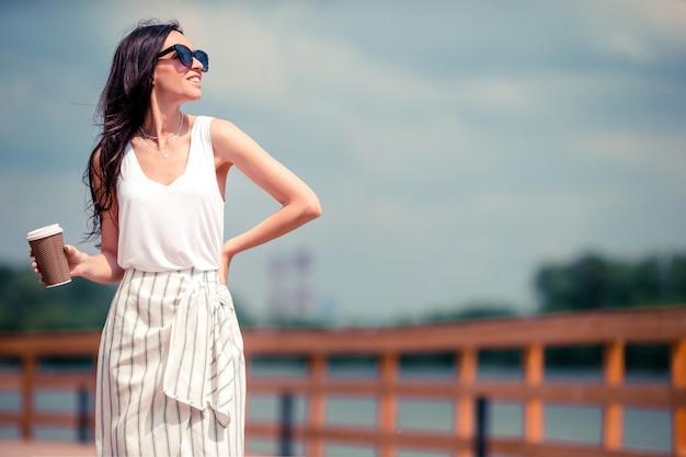 Szczęśliwa młoda miastowa kobieta pije kawę w europejskim mieście.
