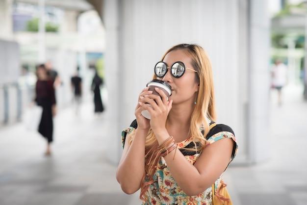 Szczęśliwa młoda miastowa kobieta pije kawę w miasto wycieczce