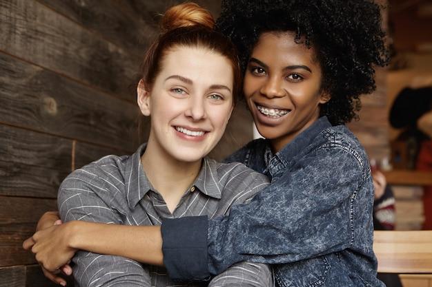 Szczęśliwa młoda międzyrasowa para homoseksualna spędza miło czas razem w nowoczesnej kawiarni