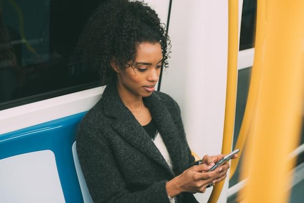 Szczęśliwa młoda murzynka siedzi wśrodku metra na telefonie komórkowym