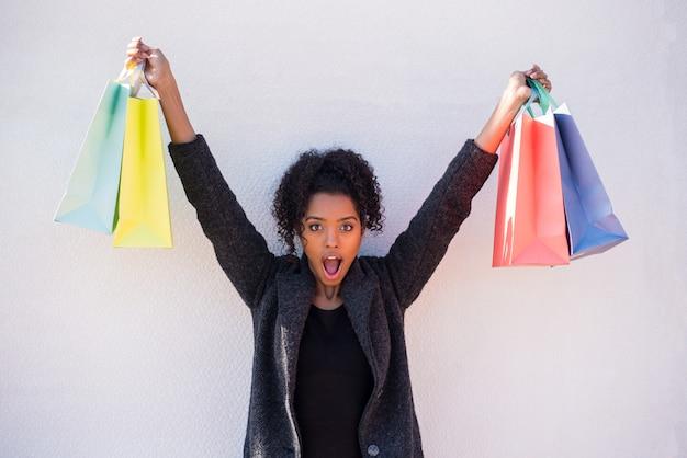 Szczęśliwa młoda murzynka z torba na zakupy przeciw białej ścianie