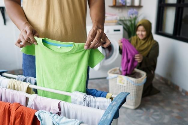 Szczęśliwa młoda muzułmanka i jej mąż razem robi pranie w domu