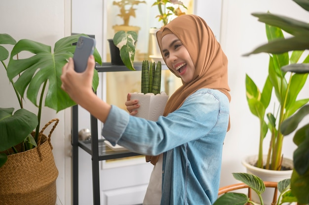 Szczęśliwa młoda muzułmanka robiąca selfie z roślinami i prowadząca wideorozmowę w domu