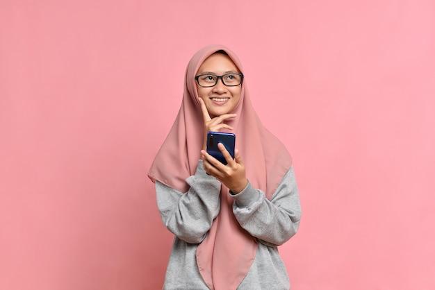 Szczęśliwa młoda muzułmańska dziewczyna trzymająca smartfon w dłoniach i odwracająca wzrok, na białym tle na różowym tle z miejscem na kopię