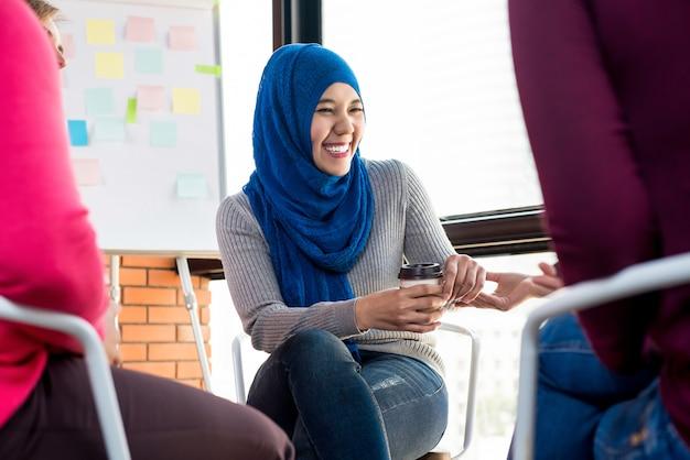 Szczęśliwa młoda muzułmańska kobieta w grupowym spotkaniu
