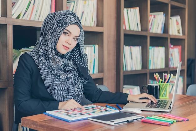 Szczęśliwa młoda muzułmańska kreatywnie projektant kobieta używa próbki palety kolorów i laptop przed półka na książki.