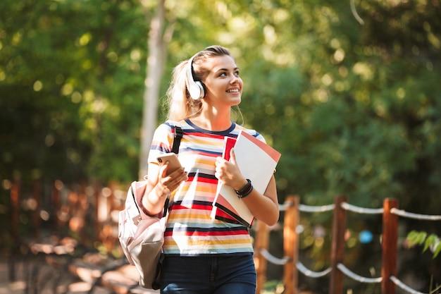 Szczęśliwa młoda nastolatka przewożąca plecak