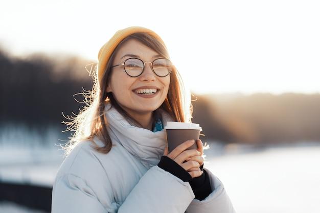 Szczęśliwa młoda nastoletnia kobieta trzyma takeaway filiżankę