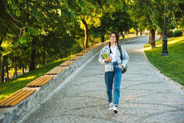 Szczęśliwa młoda nastoletnia studentka niosąca plecak i książki podczas spaceru na świeżym powietrzu w parku