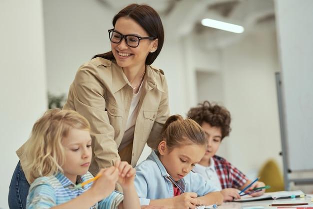 Szczęśliwa młoda nauczycielka w okularach, pomagając swoim małym uczniom w klasie, dzieci siedzące w