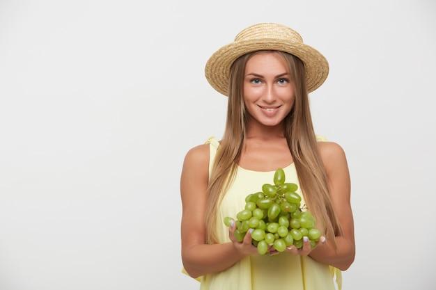 Szczęśliwa młoda niebieskooka urocza blondynka z naturalnym makijażem pokazująca swoje białe idealne zęby, uśmiechając się szeroko, pozując na białym tle z kiścią winogron