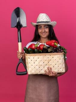Szczęśliwa młoda ogrodniczka dziewczyna w fartuchu i letnim kapeluszu trzyma skrzynię pełną warzyw i łopatę z uśmiechem na twarzy stojącej nad różową ścianą