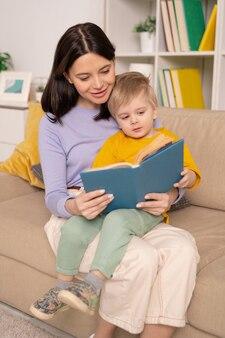 Szczęśliwa młoda ostrożna kobieta trzyma uroczego synka na kolanach siedząc na kanapie i czytając bajki podczas izolacji w domu