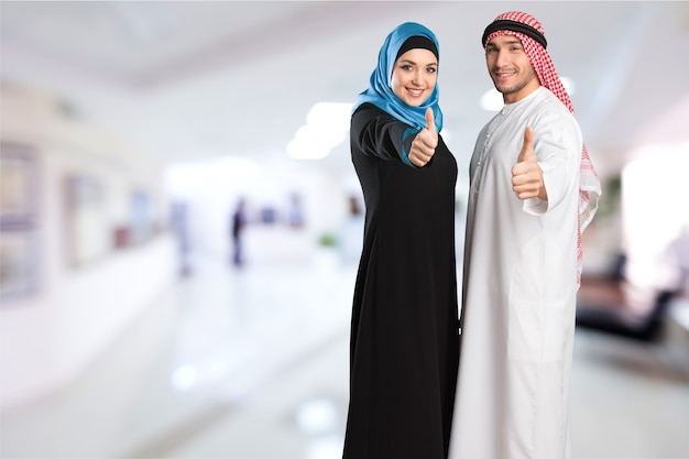 Szczęśliwa młoda para arabska z kciukami w górę