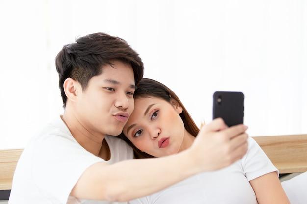 Szczęśliwa młoda para azjatów lubi robić sobie selfie na łóżku w sypialni, wesoły azjata mąż i żona mieszkają razem w sypialni. para za pomocą smartfona, aby zrobić zdjęcie selfie.