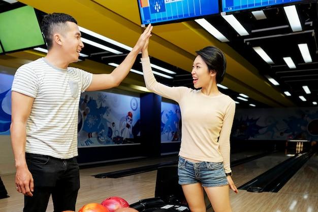Szczęśliwa młoda para azjatów przybija sobie piątkę podczas wspólnej gry w kręgle