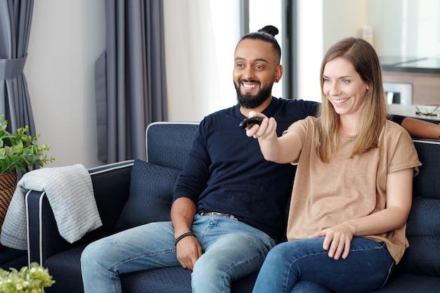 Szczęśliwa młoda para azjatów siedzi na kanapie i ogląda program w telewizji, relaksując się w koncepcji domu