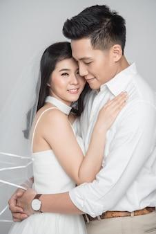Szczęśliwa młoda para azjatyckiego pana młodego i panny młodej w miłości, nosząca swobodną suknię ślubną obejmującą na białym tle