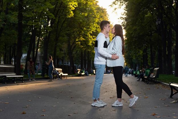 Szczęśliwa młoda para całuje w parku. pełnowymiarowy portret. pierwsza randka.