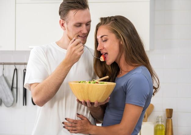 Szczęśliwa młoda para ciesząca się i przygotowująca zdrowy posiłek w domowej kuchni